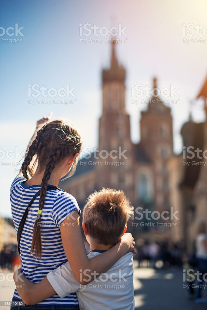 Kids visiting Krakow and looking at Mariacki Church (St. Mary) stock photo