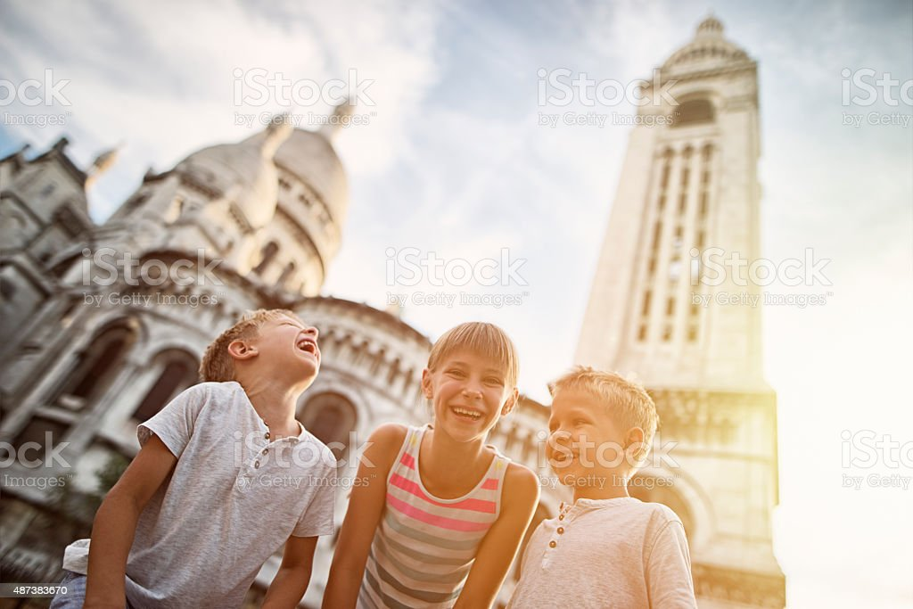 Kids visiting Paris, Sacre Coeur is visible in the background. stock photo
