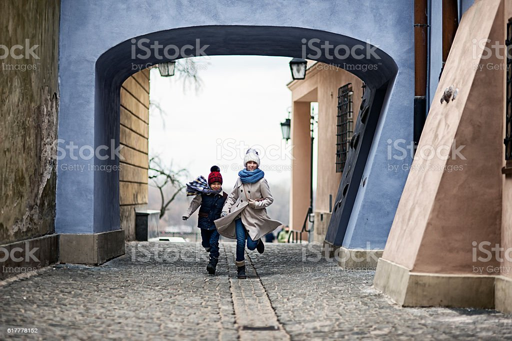 Kids visiting Warsaw -  running in old town back street stock photo