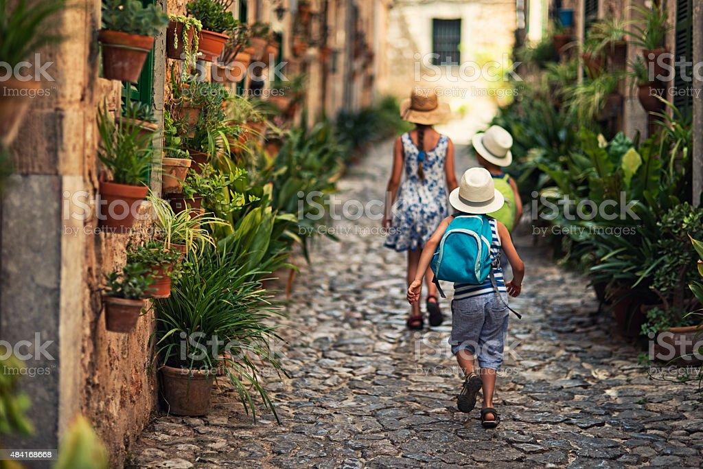 Kids walking in mediterranean street. stock photo