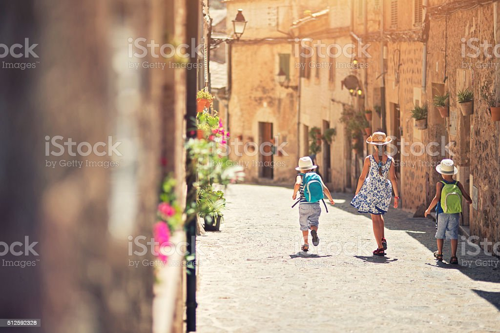 Kids walking in mediterranean street. stock photo