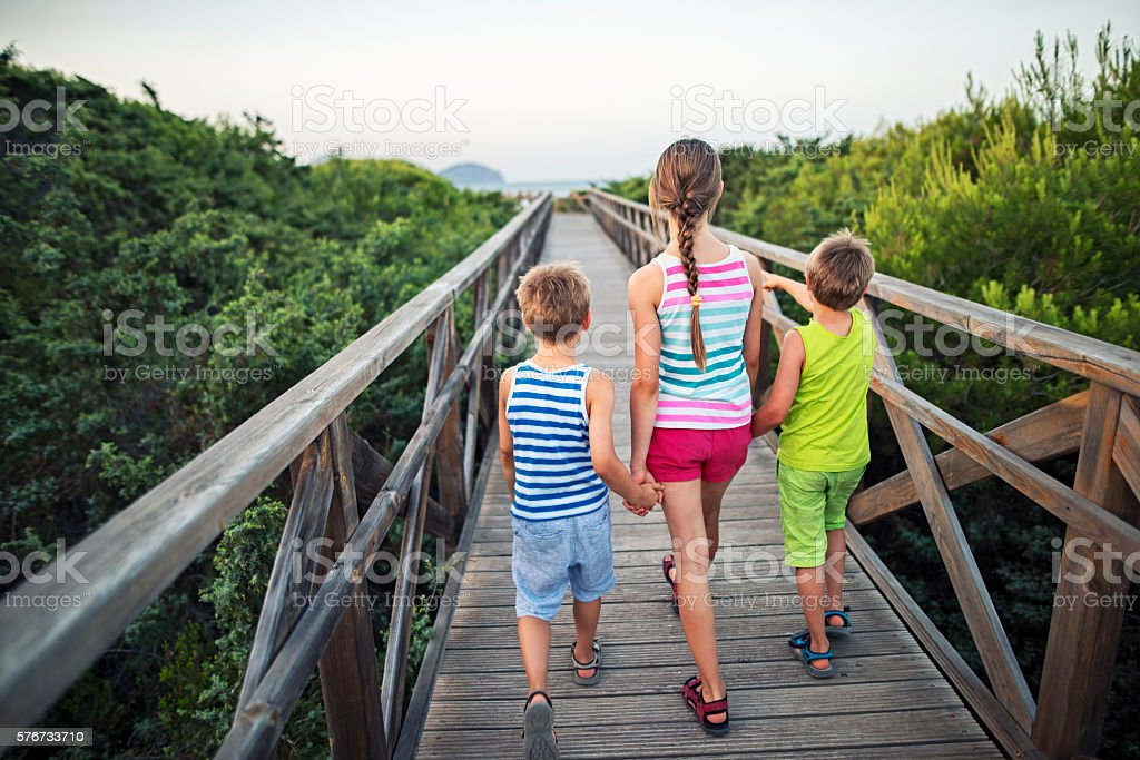 Kids walking on a ramp to the beach stock photo