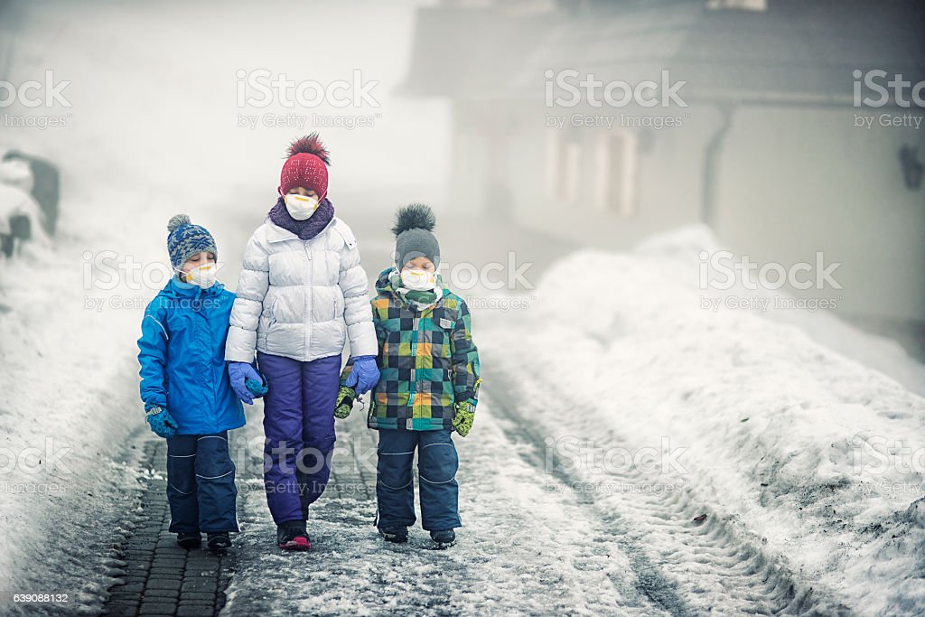Kids walking on dirty snow wearing pollution mask. stock photo