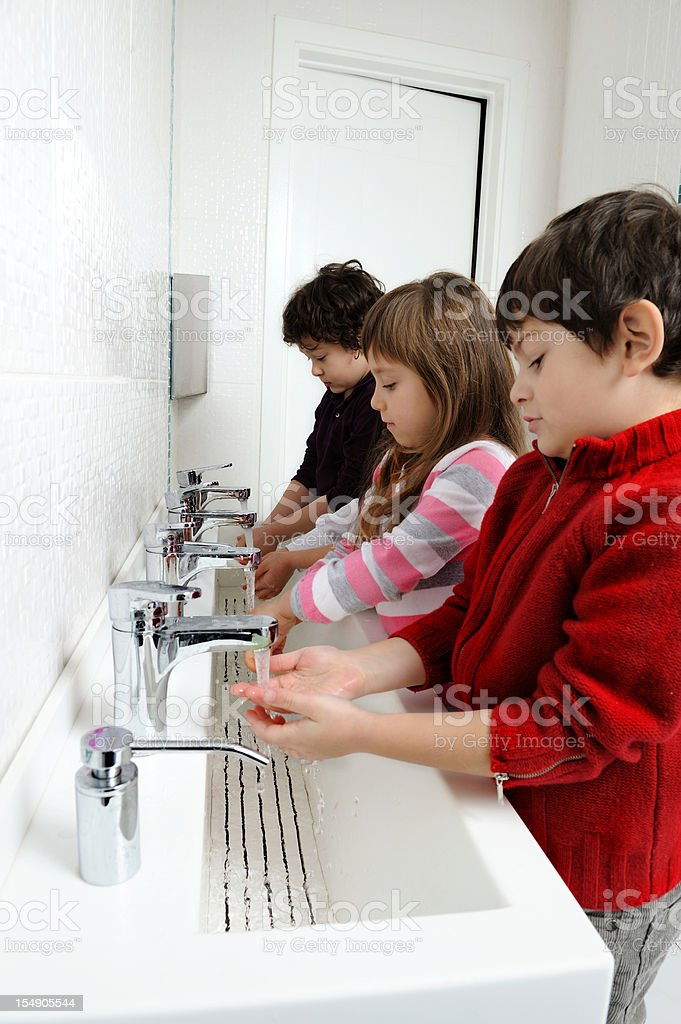Kids washing hands in bathroom royalty-free stock photo