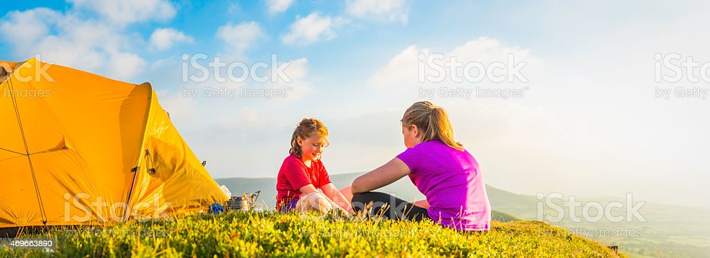 Kids wild camping on idyllic mountain top summer sunset panorama stock photo