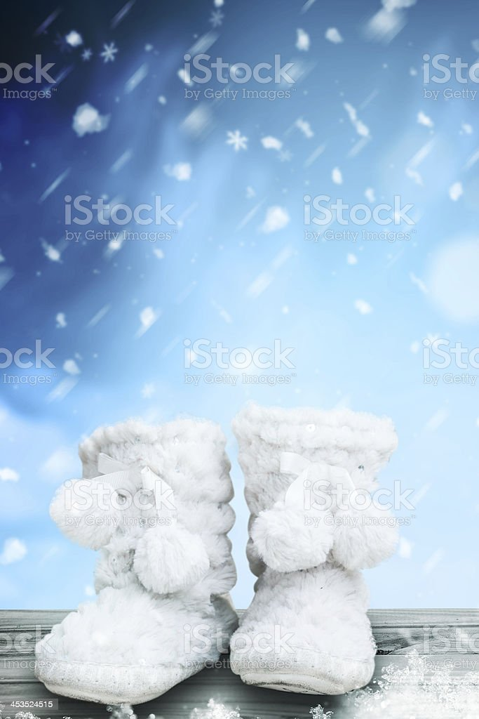 Kids winter boots on the wooden terrace stock photo