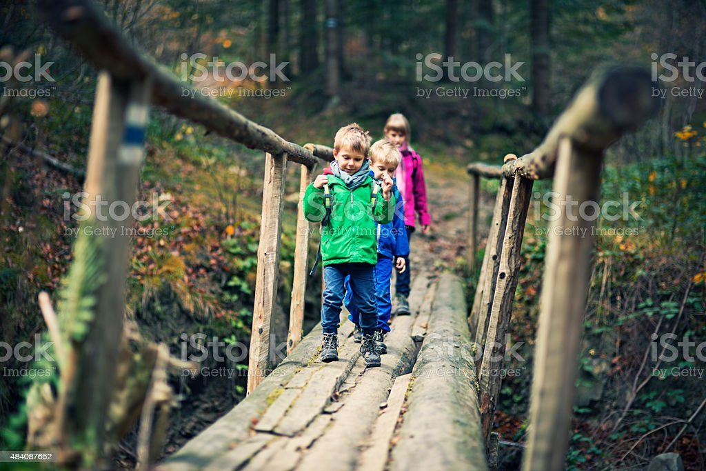Kids with backpacks hiking in autumn forest stock photo