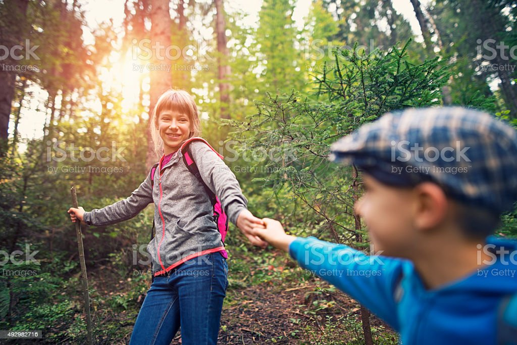 Kids with backpacks hiking in forest stock photo