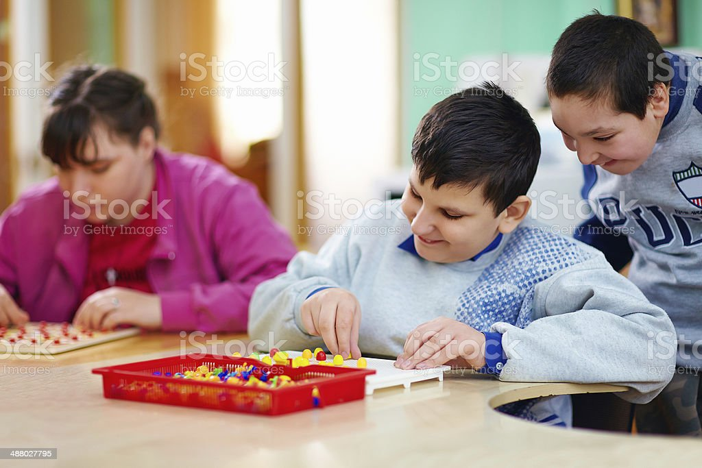Kids with disabilities work at cognitive tasks stock photo