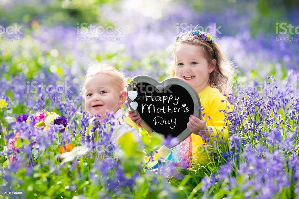 Kids with flowers and chalk board stock photo