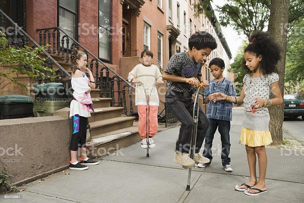 Kids with pogo sticks stock photo