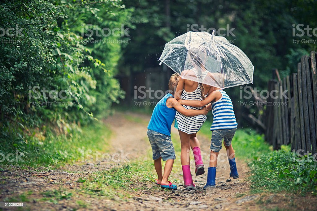 Kids with umbrella enjoying rain. stock photo