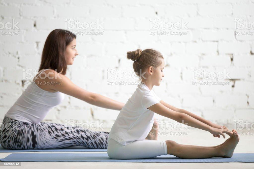 Kids yoga teacher training with a child a paschimottanasana pose stock photo