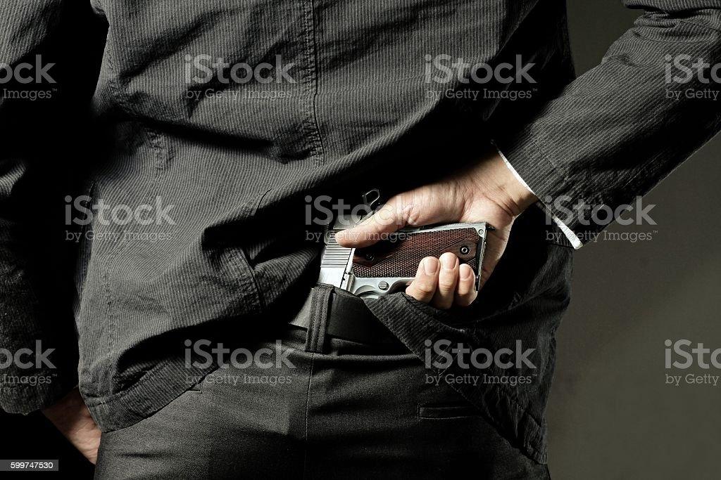 killer or gangster concealing gun stock photo