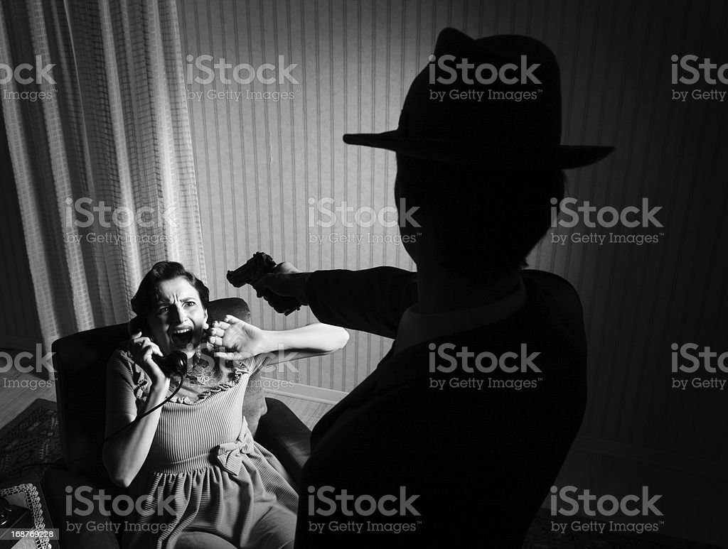 Killer pointing the gun at a terrified woman stock photo