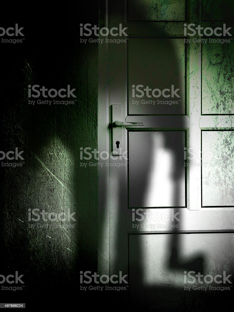 Killer with axe lurking in the darkness at the door stock photo