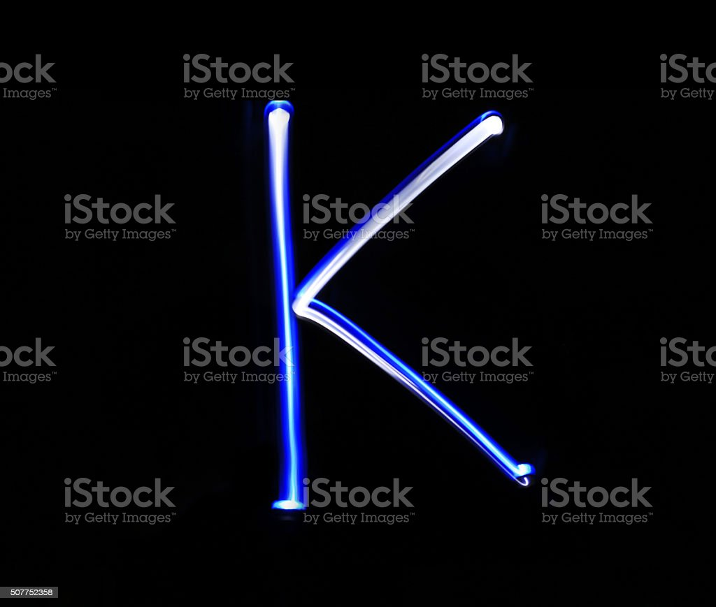 K Kilo alphabet hand writing blue light  over black background. stock photo