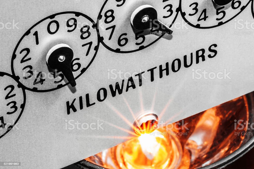 Kilowatthour electric meter register dials with light bulb shining below stock photo