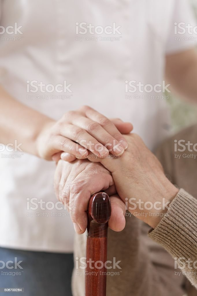 Kind caregiver holding senior man stock photo