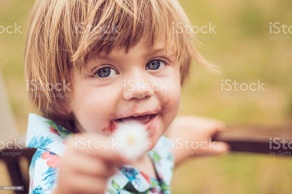 Kind charming kid gifting Daisy flower stock photo