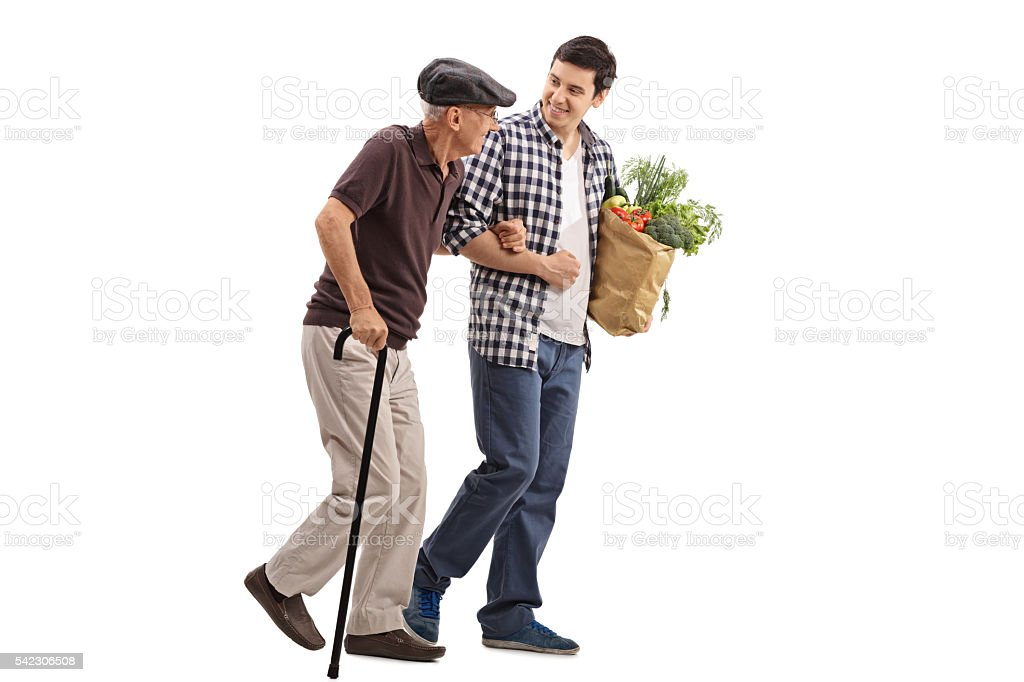 Kind man helping a senior with groceries stock photo