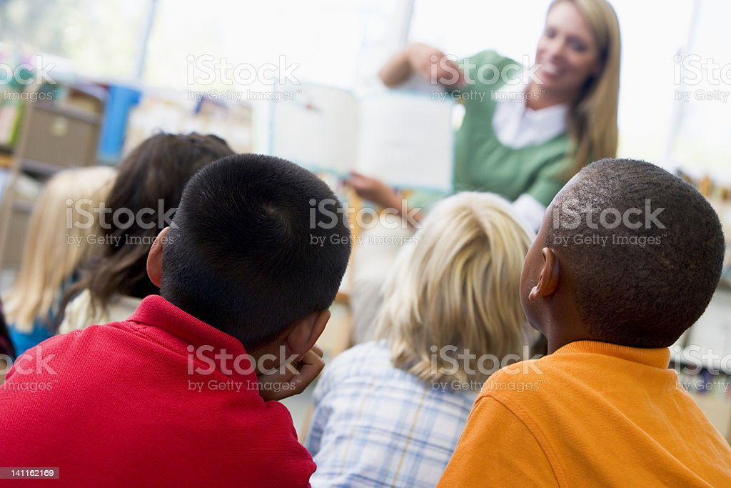 Kindergarden teacher reading to children in library royalty-free stock photo