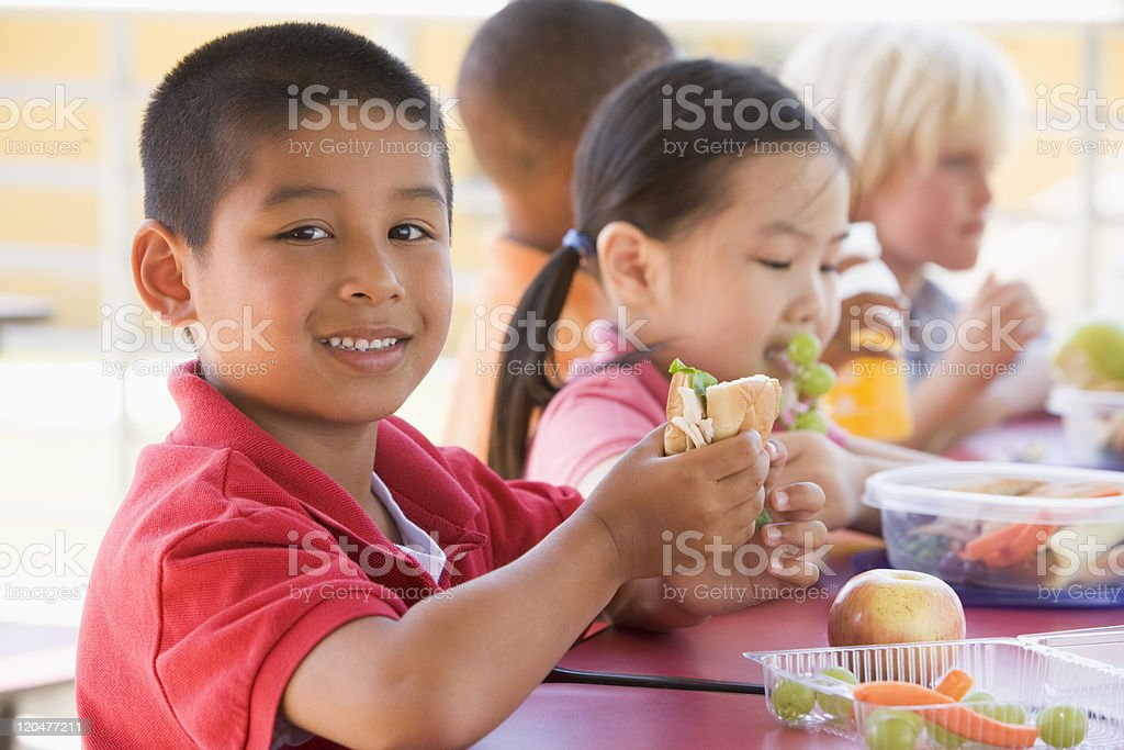 Kindergarten children eating lunch stock photo