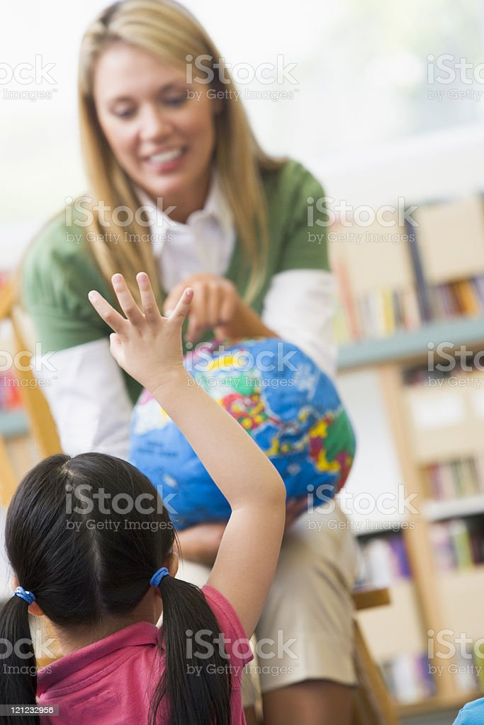 Kindergarten teacher and children looking at globe royalty-free stock photo