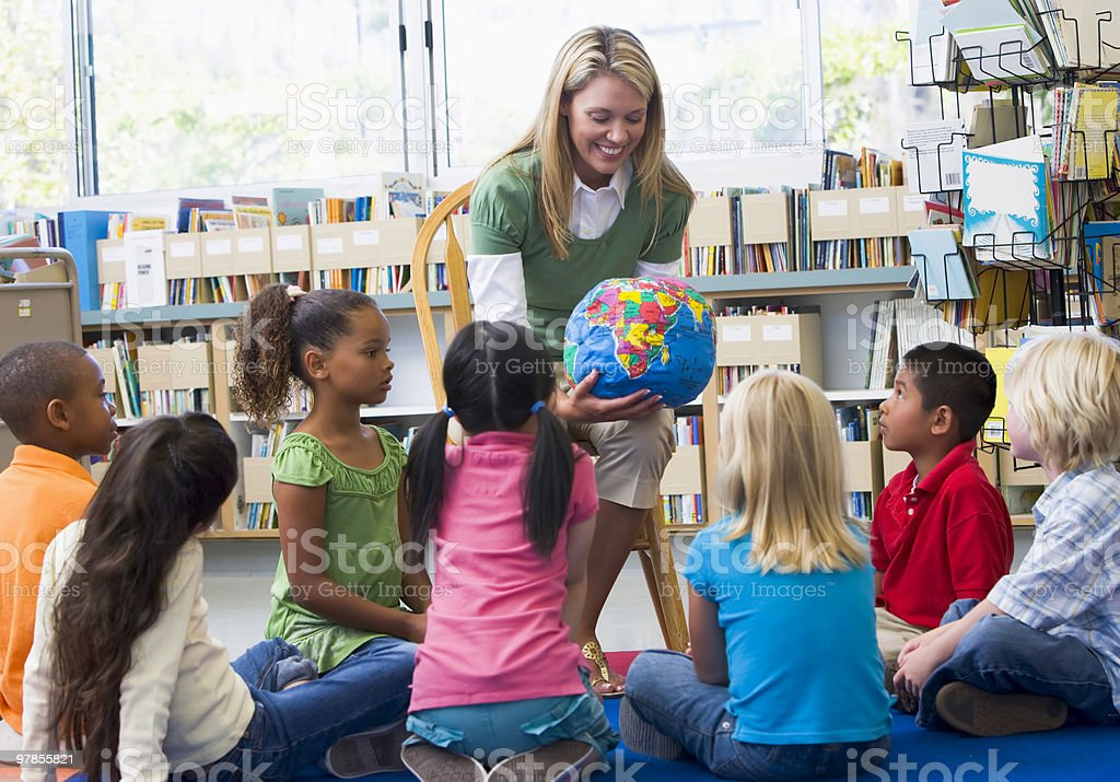 Kindergarten teacher and children looking at globe stock photo