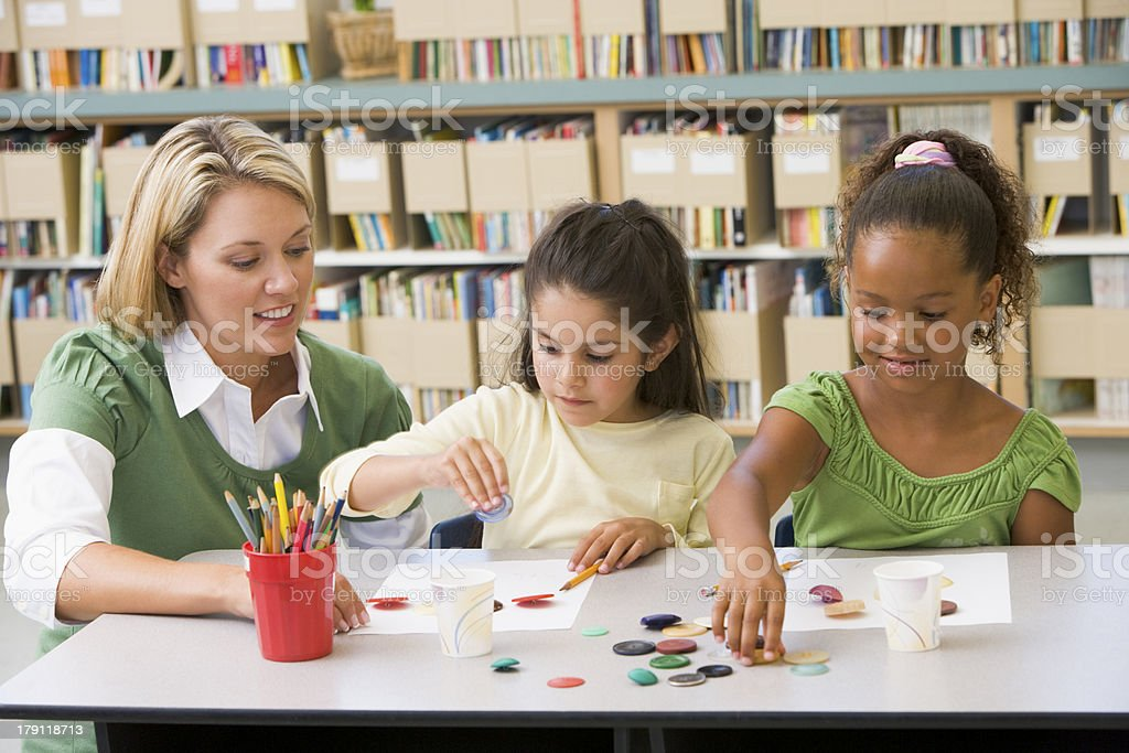 Kindergarten teacher and students in art class stock photo