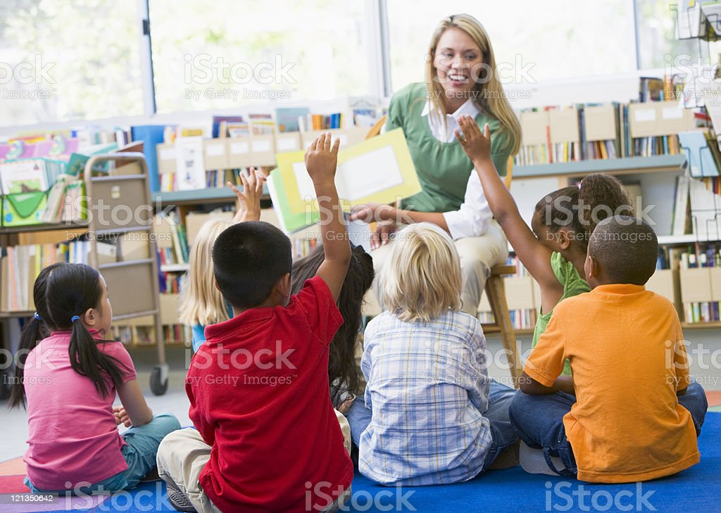 Kindergarten teacher reading to children stock photo