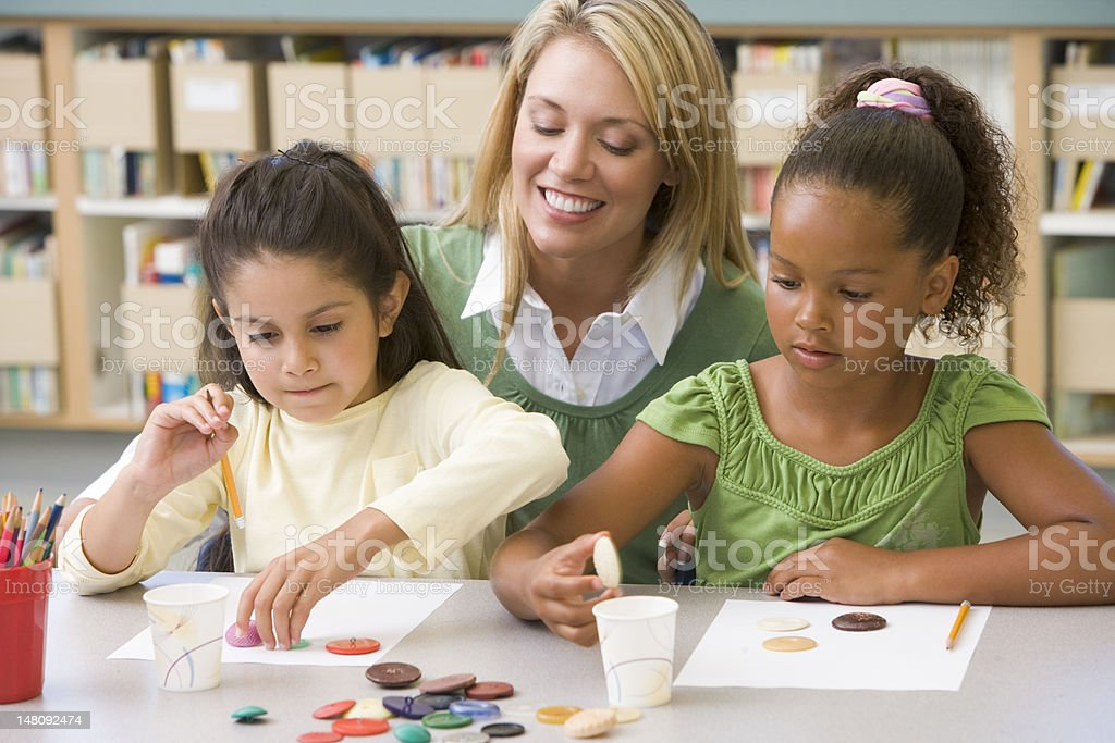 Kindergarten teacher sitting with students in art class stock photo