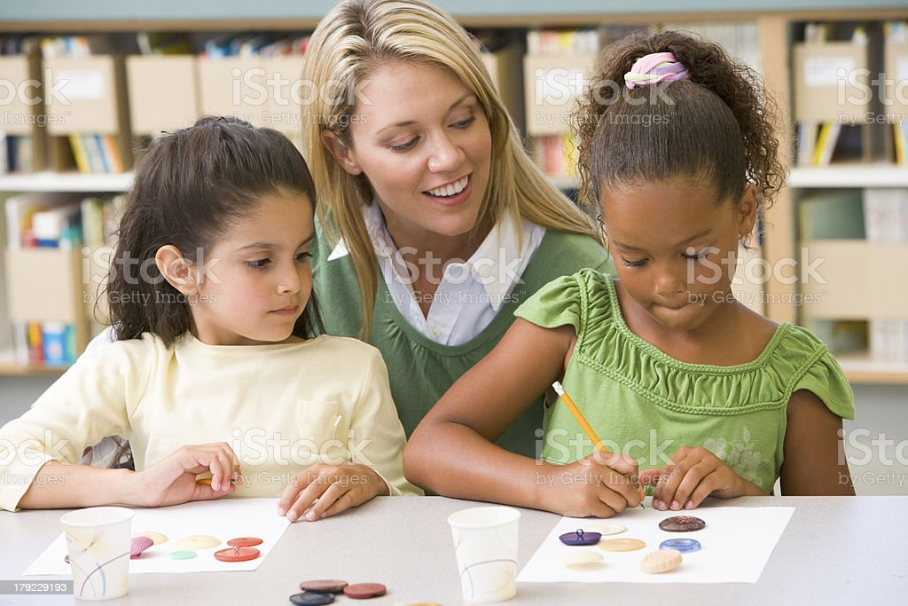 A kindergarten teacher sitting with two students in art stock photo