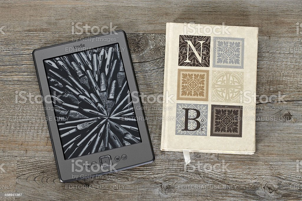 KIndle eReader side by sid with an old printed notebook stock photo