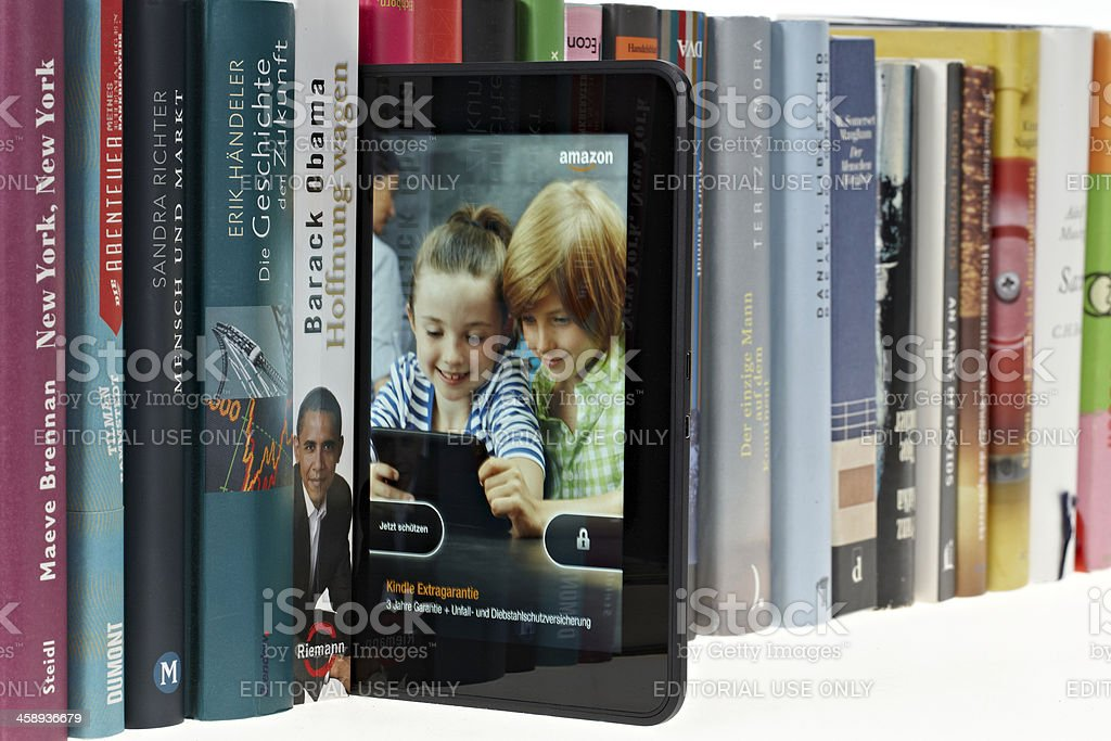 KIndle fire HD in a row of real books stock photo