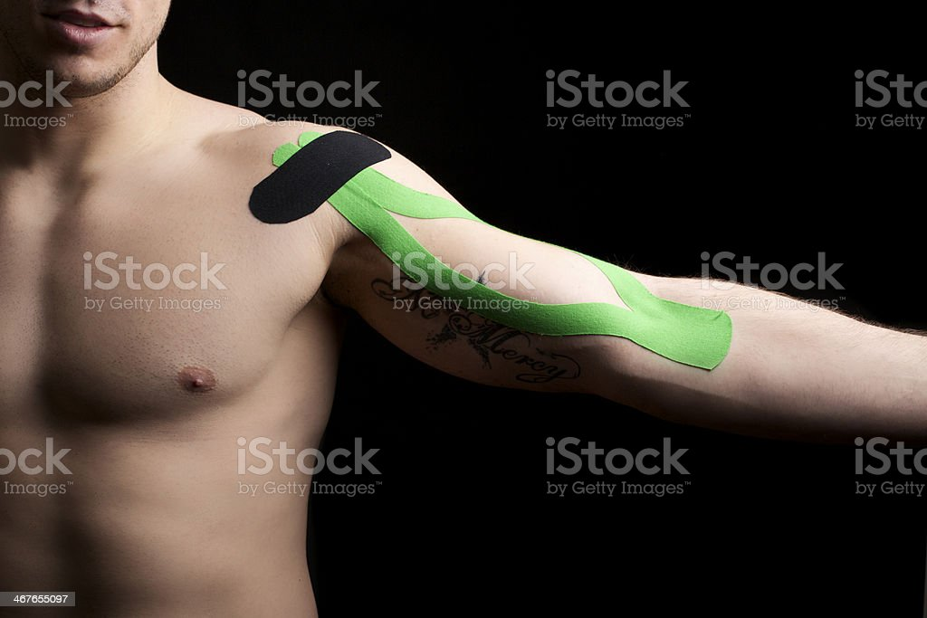 Kinesiotape on young male athlete's bicep. stock photo