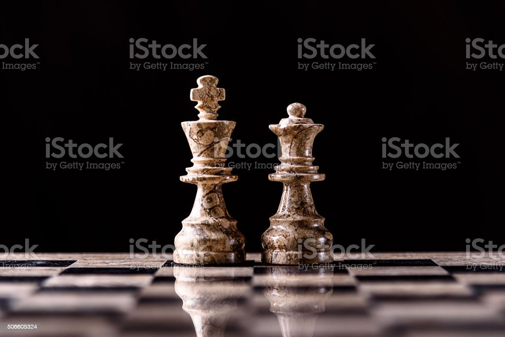 King and Queen chess pieces on board stock photo