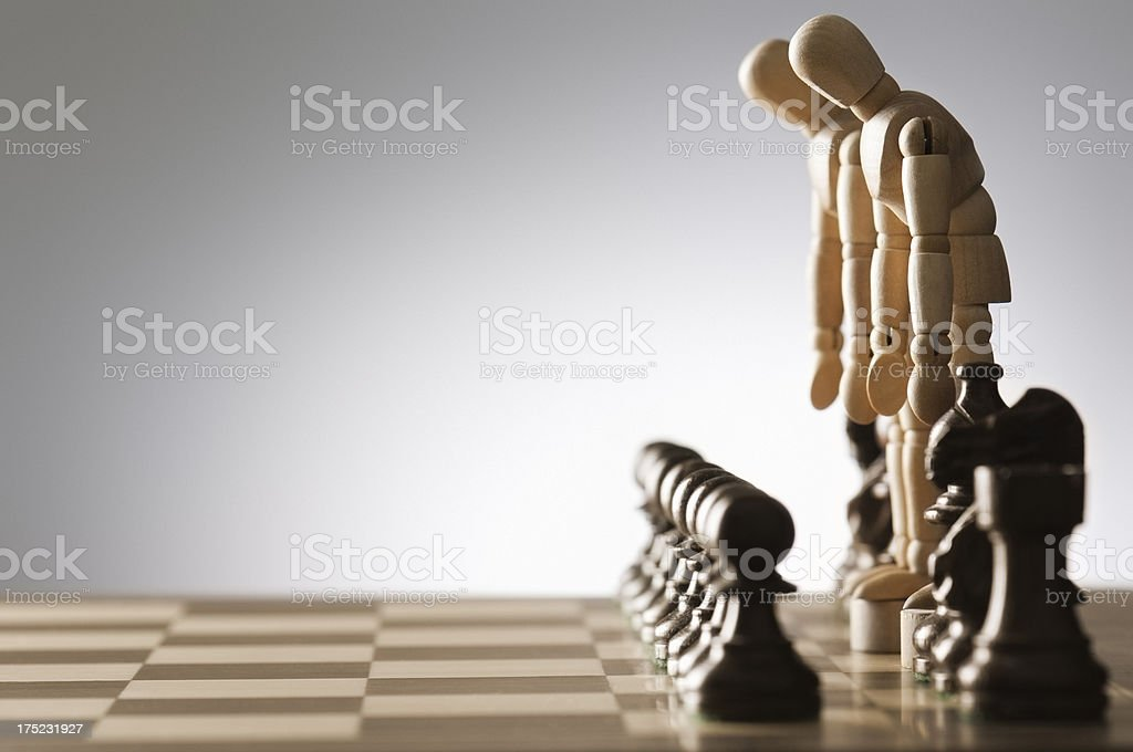 King and Queen chess pieces stand defeated on chess board stock photo