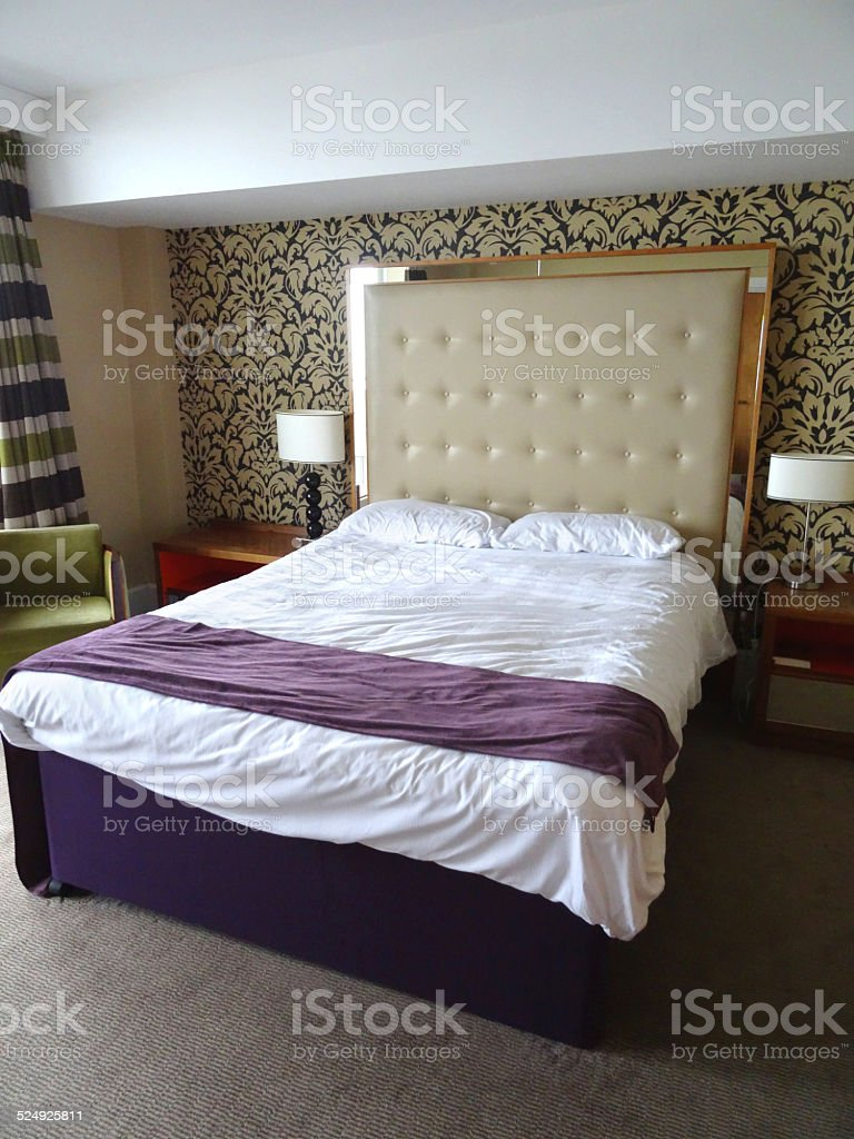 Kingsize double bed, large beige studded leather headboard, white-sheets, bedside-lamps stock photo