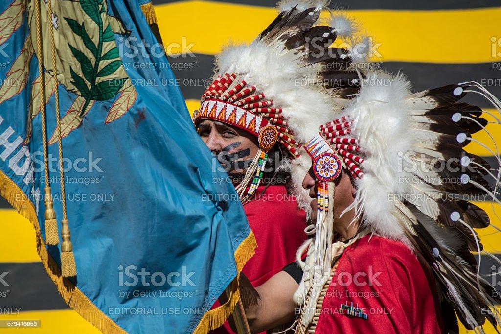 Kiowa men with Oklahoma flag during color guard at Pow-wow. stock photo