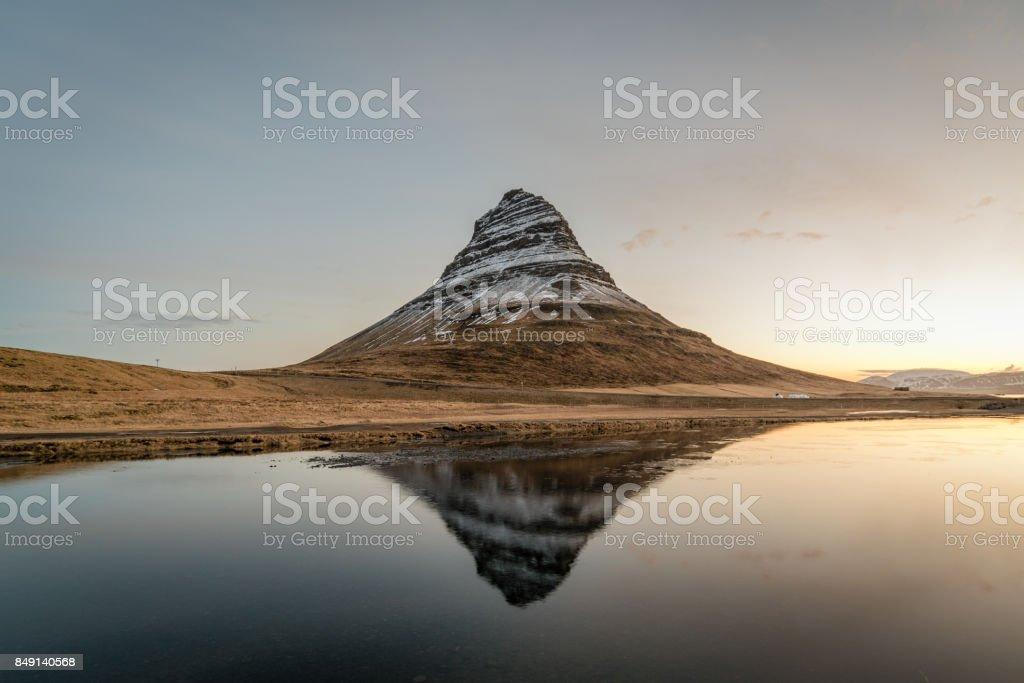 Kirkjufell reflecting on water under clear sky befor sunrise. stock photo