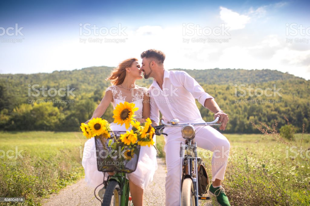 Kiss of romantic young couple on bicycles stock photo