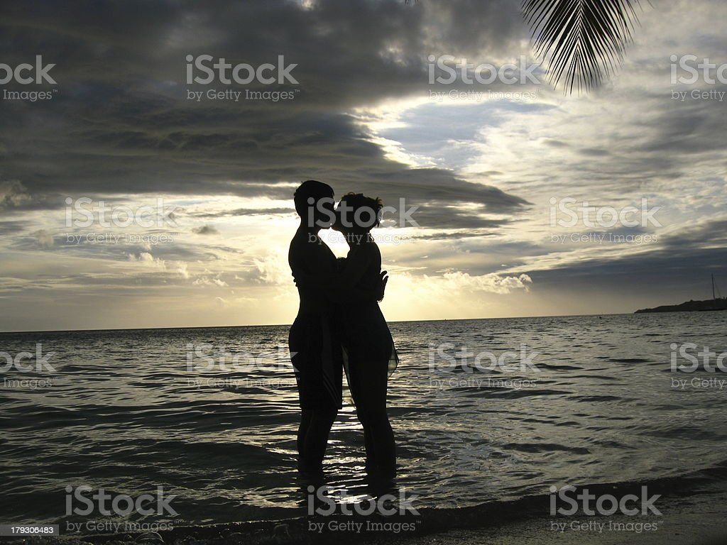 kissing couple in front of the sunset royalty-free stock photo