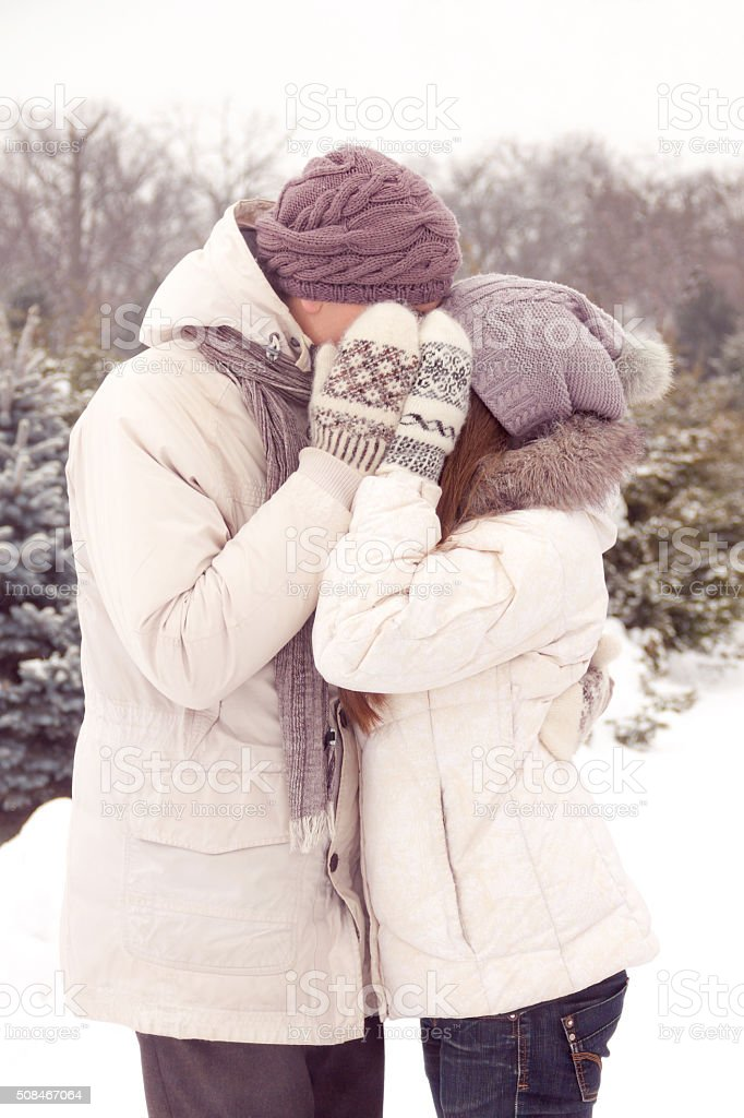 Kissing couple in park in winter stock photo