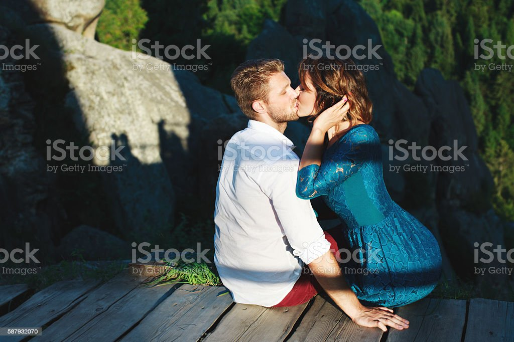 Kissing couple sitting on wooden path stock photo