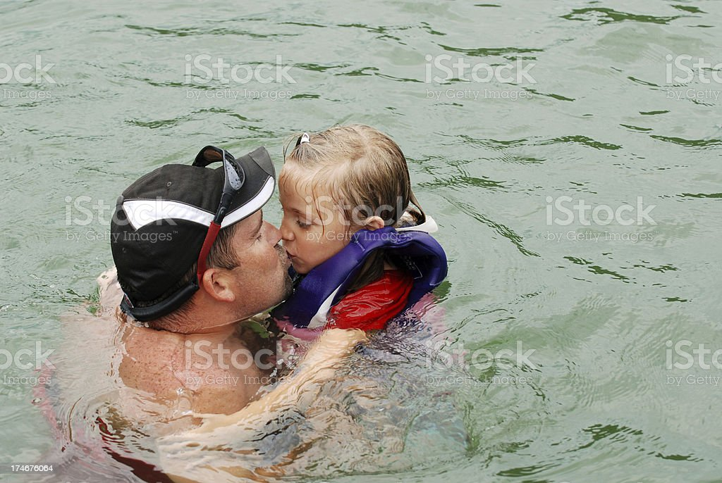 Kissing Daddy in the Lake stock photo