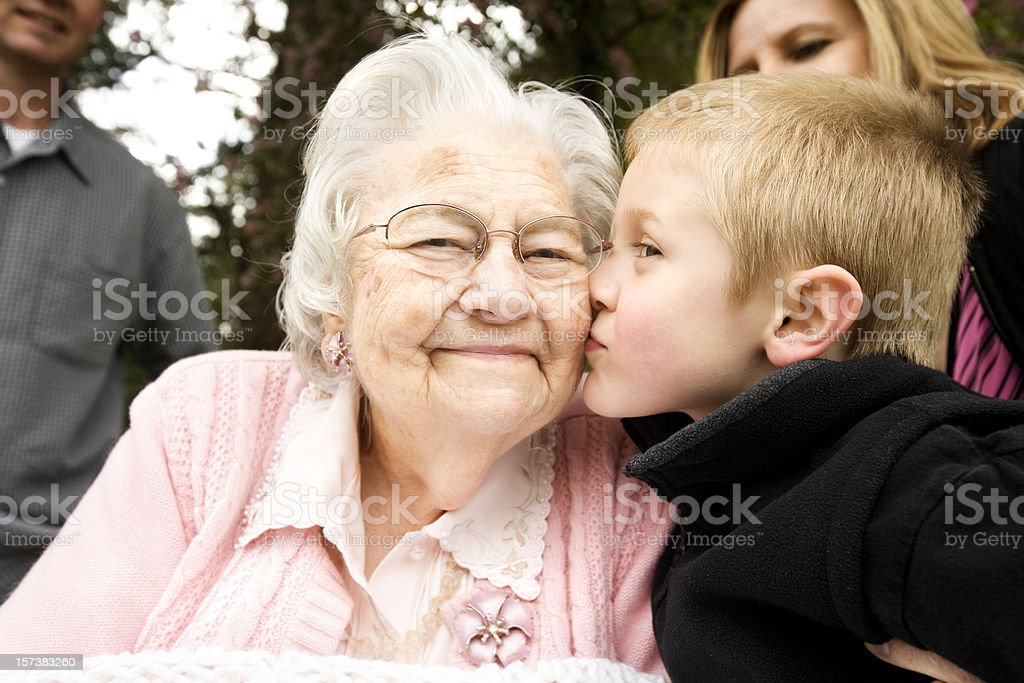 Kissing Great Grandma 80 years grandson retirement senior stock photo