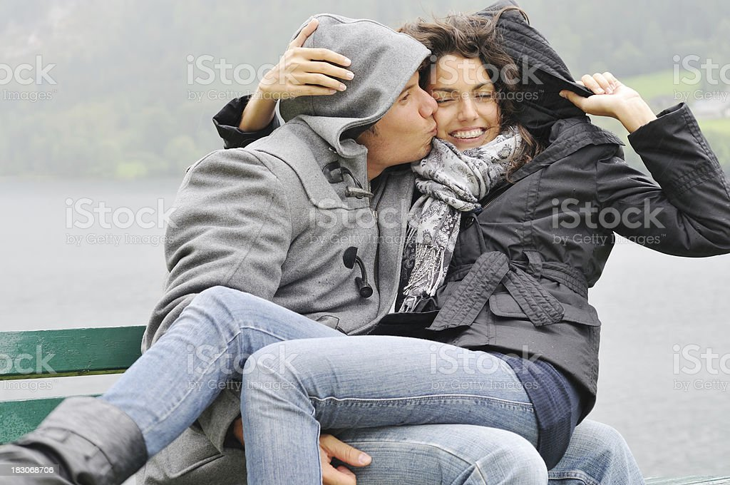 kissing in the rain and wind stock photo