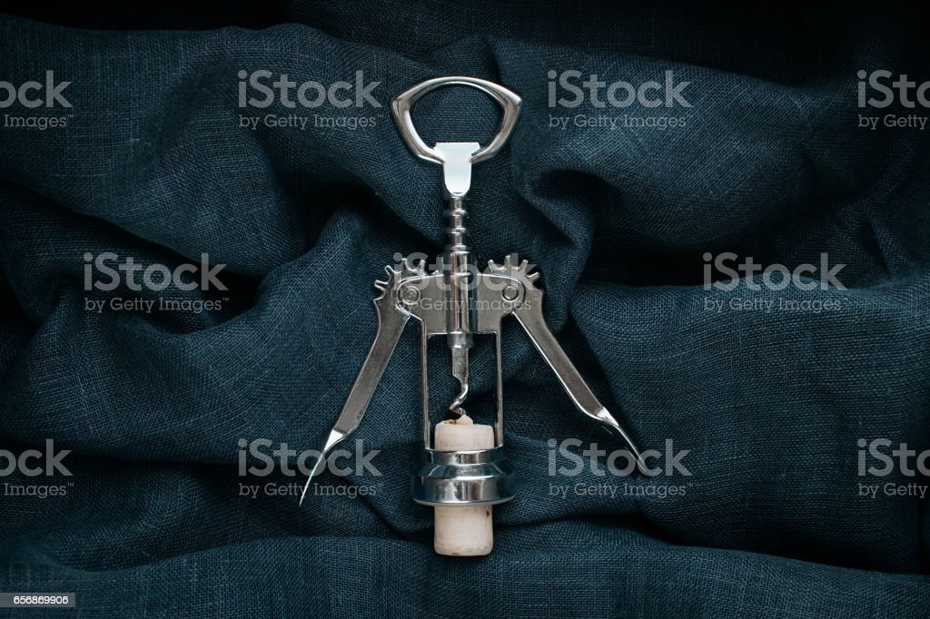 Kitchen accessory. Metal bottle opener with cork on textile...