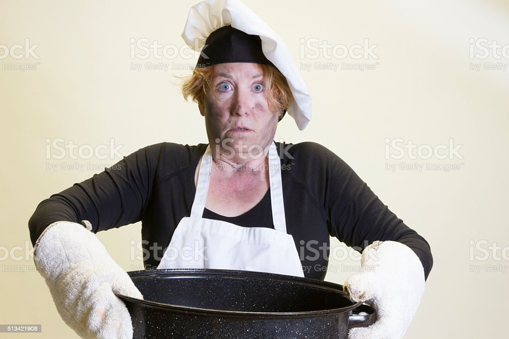 Kitchen disasters, roasting pan and chefs hat stock photo